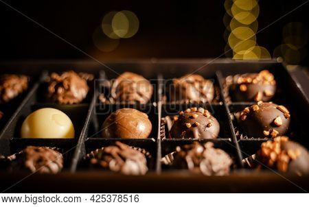 Delicious Chocolate Candies Or Truffle Balls In Box On Table Against Light Bokeh. Assorted Chocolate