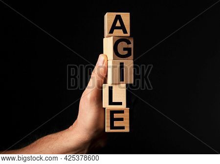 Agile Word On Wooden Blocks In Male Hand Over Black Background With Copy Space For Text.