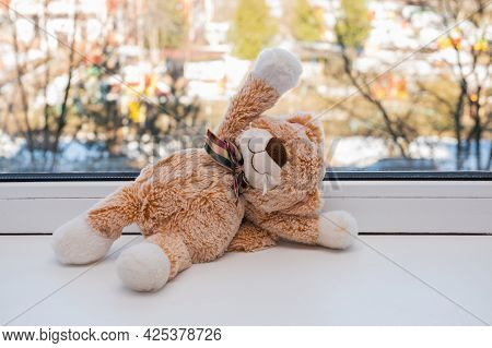 Small Plush Toy Kitten With A Bow Sits On A White Windowsill And Waves Its Paw. The Sun Is Shining O