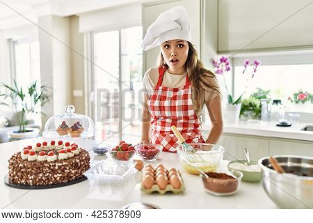 Beautiful young brunette pastry chef woman cooking pastries at the kitchen afraid and shocked with surprise expression, fear and excited face.