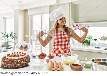 Beautiful young brunette pastry chef woman cooking pastries at the kitchen looking confident with smile on face, pointing oneself with fingers proud and happy.