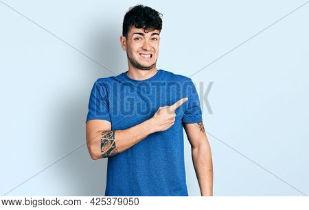 Young hispanic man wearing casual t shirt pointing aside worried and nervous with forefinger, concerned and surprised expression