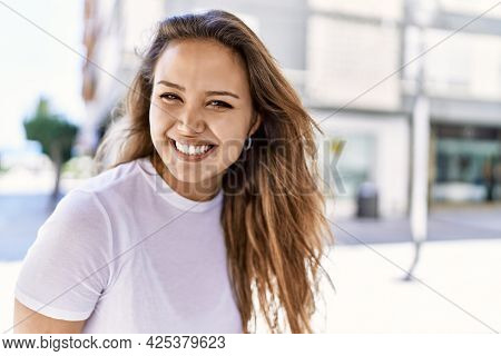 Attractive and beautiful hispanic woman smiling happy on a sunny day outdoors. Pretty brunette girl with positive smile looking confident at the city