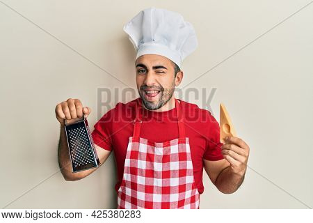 Young hispanic man wearing professional cook uniform holding grater and cheese winking looking at the camera with sexy expression, cheerful and happy face.
