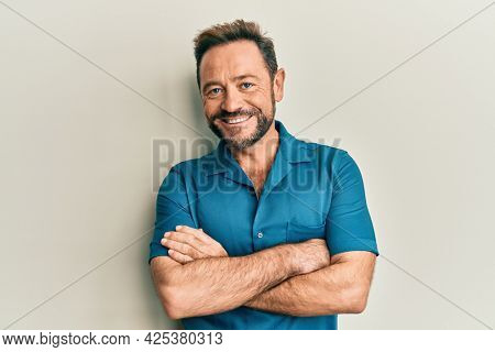 Middle age man wearing casual clothes happy face smiling with crossed arms looking at the camera. positive person.