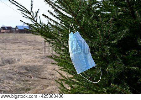 On A Bright Sunny Day, A Disposable Medical Mask Hangs On A Tree Branch. Environmental Pollution Pro