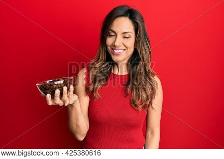 Young latin woman holding bowl with raisins looking positive and happy standing and smiling with a confident smile showing teeth