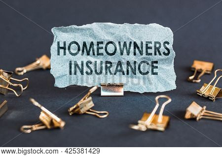 A Scrap Of Blue Paper With Clips On A Gray Background With The Text - Homeowners Insurance.