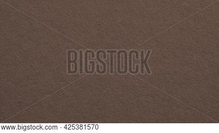 The Surface Of Dark Brown Cardboard. Paper Texture With Cellulose Fibers. Paperboard Wallpaper Or Ba