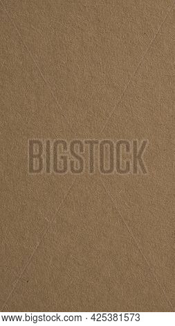 The Surface Of Brown Cardboard. Paper Texture With Cellulose Fibers. Vertical Background With A Past