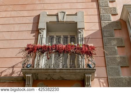 Detailed View On Front Facade Window And Small Metallic Balcony With Decorative Flowers. Coral And G