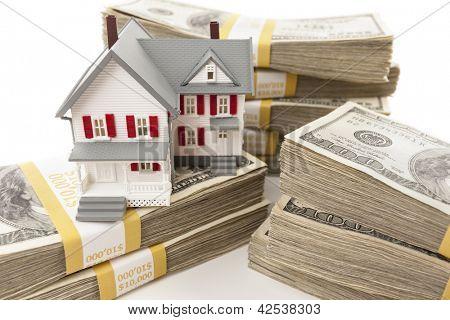 Pilhas de notas de cem dólares, com pequena casa.