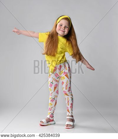 Studio Shot Of Cheerful Little Red-haired Girl Child Wearing Summer Fashion Outfit Spreading Arms Fl
