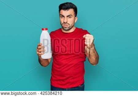 Hispanic man with beard holding liter bottle of milk annoyed and frustrated shouting with anger, yelling crazy with anger and hand raised