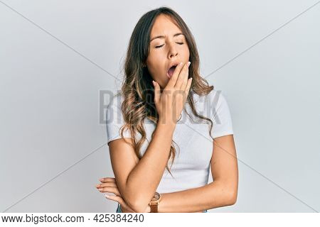 Young brunette woman wearing casual white t shirt bored yawning tired covering mouth with hand. restless and sleepiness.
