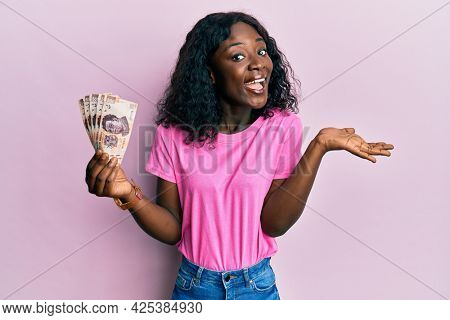 Beautiful african young woman holding 500 mexican pesos banknotes celebrating achievement with happy smile and winner expression with raised hand