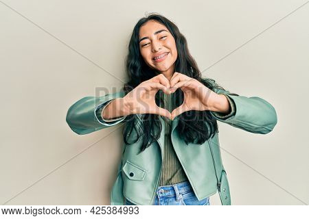 Hispanic teenager girl with dental braces wearing green leather jacket smiling in love doing heart symbol shape with hands. romantic concept.