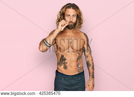 Handsome man with beard and long hair standing shirtless showing tattoos mouth and lips shut as zip with fingers. secret and silent, taboo talking
