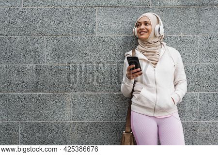 Smiling mid aged muslim woman in headphones holding mobile phone leaning on a wall on a street