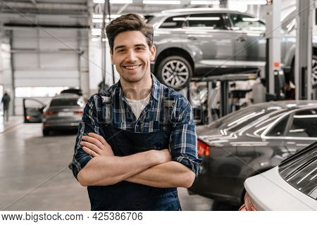 Young white car mechanic smiling while standing in garage indoors