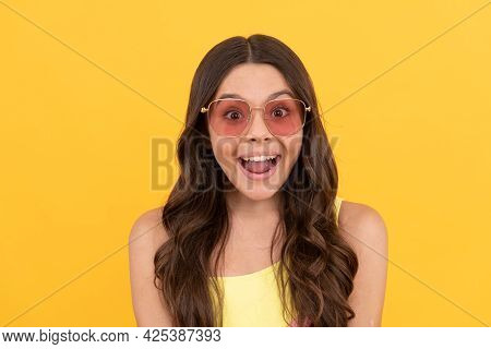 Amazed Teen Girl In Summer Glasses Has Curly Hair On Yellow Background, Amazement And Surprise