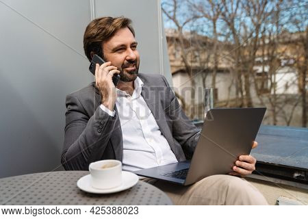 Smiling mid aged businessman sitting at the hotel terrace talking on mobile phone