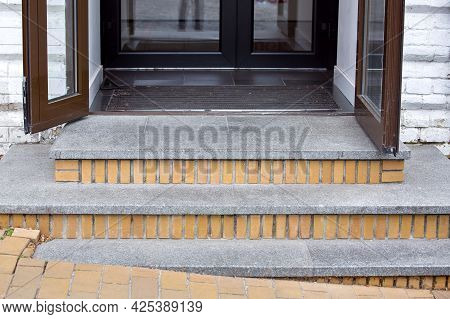 Threshold With Granite Steps Of A Brick House With Brown Iron Doors With Glass And Foot Mat Close-up