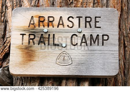 June 29, 2021 In Big Bear, Ca:  Wooden Sign With Rust Posted On A Pine Tree Taken At Arrastre Trail