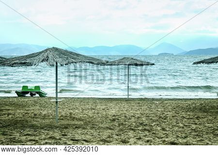 Panorama Of A Beach With Parasol Sun Umbrella During A Cloudy Rainy Afternoon On The Prespa Lake On