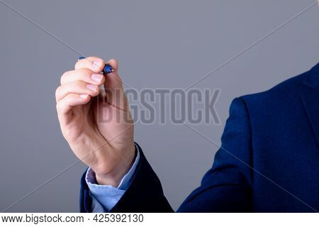 Midsection of caucasian businessman holding pen, isolated on grey background. business technology, communication and growth concept.
