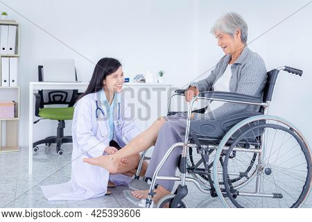 Female Doctor Examining Senior Woman's Leg While Sitting On Wheelchair. Elderly Patient Care And Hea