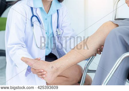 Close Up Of Female Doctor Examining Senior Woman's Leg While Sitting On Wheelchair. Elderly Patient