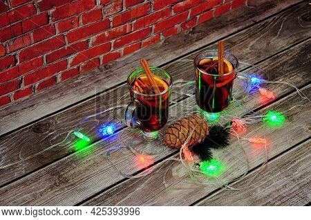 Two Glasses Of Hot Red Wine, A Pine Cone And A Branch Of Needles Lie On A Wooden Table In A Heap Of