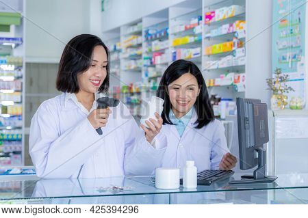Two Asian Pharmacists Working In A Pharmacy Drugstore. Health Care And Medical Concept.pharmacist Sc