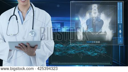 Mid section of female doctor using digital tablet against medical data processing on blue background. medical research and science technology concept