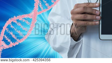 Mid section of male doctor holding a digital tablet against dna structure on blue background. medical research and science technology concept