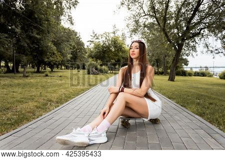 Attractive Woman  In Short Dress  Sitting On The Skateboard And Looking Away Smiling While Spending