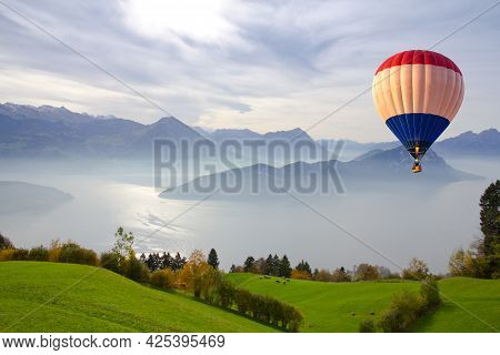 Aerial View Of Hot Air Balloon Flying Over Mount Rigi. Scenic View Of Fog Over The Lake At Mount Rig