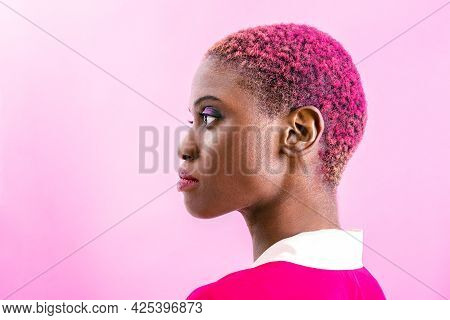 Portrait Of A Black Short Haired Woman In Front Of A Pink Background