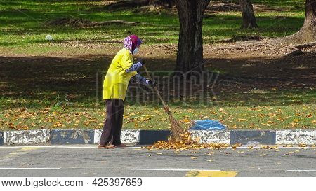 Labuan Ft,malaysia-may 17,2021:a Street Cleaner On The Job With Stick In Labuan Street At Labuan Ft,