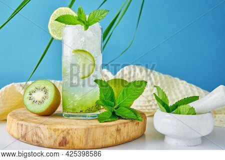Summer Refreshment Drink. Glass Of Water With Kiwi, Lime And Mint On Blue Background. Homemade Lemon