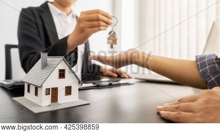 Real Estate Agent Holding A Key And Asking Costumer For Contract To Buy, Get Insurance Or Loan Real