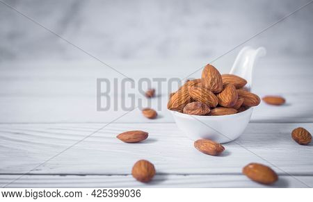 Tasty Organic Peeled Almond Snack In White Ceramic Bowl On White Wooden Background With Copy Space.c