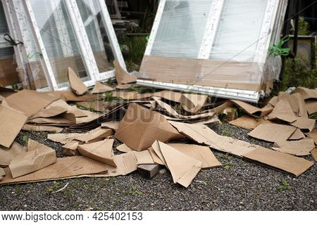 Torn Cardboard Boxes In The Foreground And A Stack Of New Pvc Windows In The Blurred Background