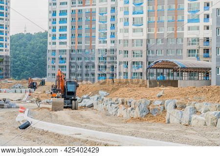 Daejeon; South Korea; June 20, 2021: Backhoe Parked On Dirt Road In Front Of Unfinished Highrise Apa