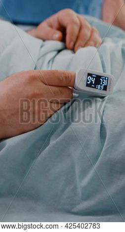 Closeup Of Sick Man Patient Resting In Bed With Medical Oximeter On Finger. Surgeon Doctor Checking