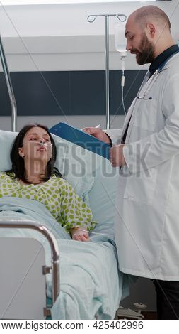 Practitioners Doctors Monitoring Sick Woman Writing Sickness Treatment On Clipboard During Medical A
