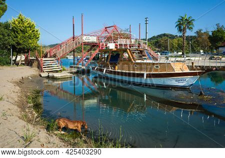 Demre, Turkey - 21 October, 2019: Dog drinks water from river, The pleasure boat is moored in quiet river near red bridge over river. On the Lycian way hiking trail