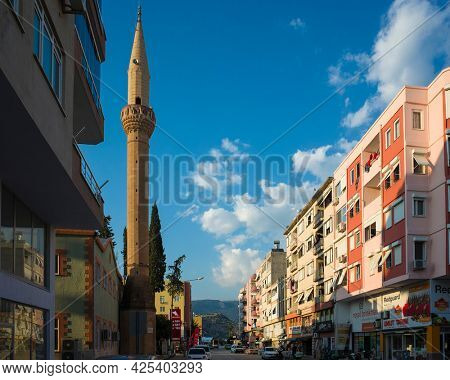 Demre, Turkey - 21 October, 2019: Mosque minaret, residential buildings and street in Demre town, Turkish city view
