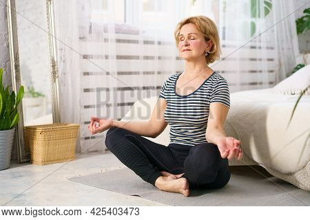 Mature Caucasian Woman In Casual Clothes Sitting In The Lotus Position On The Mat At Home. The Conce
